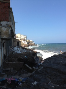 These living quarters at the sea have open windows and doors and trash piled high alongside. It is not the wealthy who have the best views in Algiers.